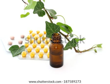Bottle of essential oil, tablets and branch of ivy isolated on white background - stock photo