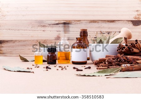 Bottle of essential oil with cinnamon stick ,star anise ,bay leaves with selective focus on old wooden background . - stock photo