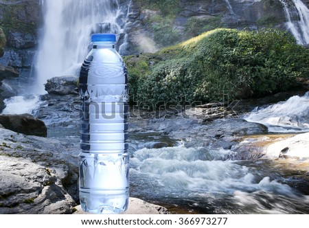 Bottle of fresh mineral water with waterfalls in background - stock photo
