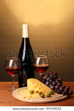Bottle of great wine with wineglasses and cheese on wooden table on brown background - stock photo