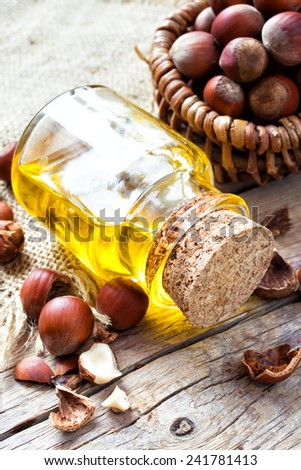 Bottle of  healthy nut oil and basket with hazelnuts on old kitchen table. Top view. - stock photo
