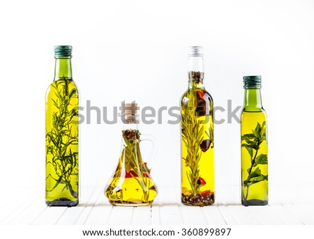 Bottle of homemade oil with herbs and spices on white background. Free space for text. - stock photo