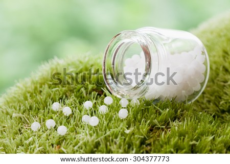 Bottle of homeopathy globules on green moss. Selective focus. - stock photo
