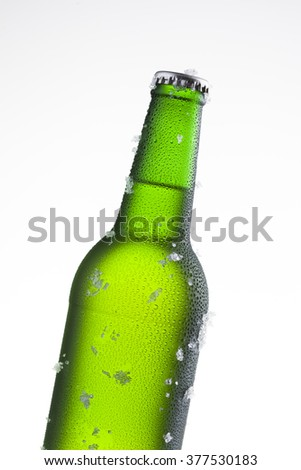 Bottle of ice cold beer with ice and drops - stock photo
