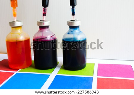 Bottle of ink printer has three colors. Colors is red, yellow and blue with syringe on colored paper. - stock photo
