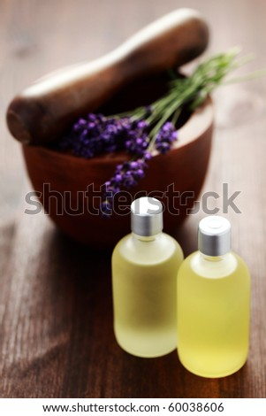bottle of lavender massage oil with mortar and pestle - beauty treatment - stock photo
