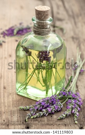 bottle of lavender oil with fresh flowers on wooden background. apothecary herbs. selective focus - stock photo