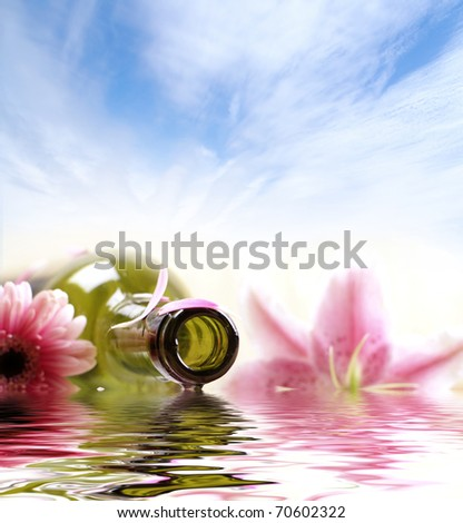 Bottle of massaging oil over spa background - stock photo