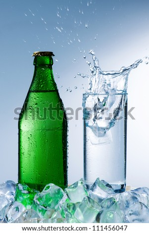 bottle of mineral water with ice and a glass with water splash on a blue background - stock photo