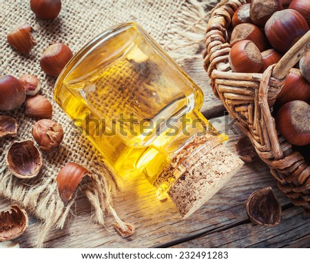Bottle of nut oil and basket with filberts on old kitchen table. Top view. - stock photo