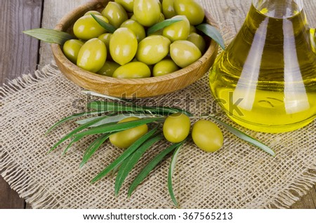 Bottle of olive oil and olives on a wooden table - stock photo
