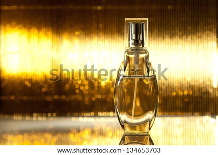 Bottle of perfume on abstract golden background - stock photo
