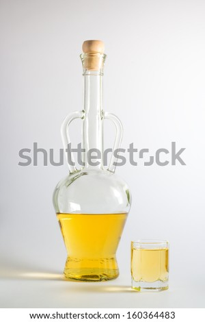 Bottle of plum brandy with a brandy glass, isolated on white background - stock photo