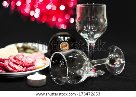Bottle of red dry wine with wineglasses and candle on a celebratory table. Colorful bokeh background - stock photo