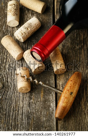 Bottle of red wine and corks on wooden table - stock photo