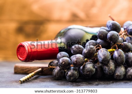 Bottle of red wine and grapes on wooden background with copyspace - stock photo