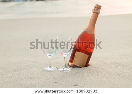 Bottle of red wine and two glasses on the white sandy beach - stock photo