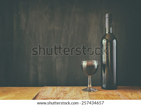 bottle of red wine and wine glass over wooden table. image is filtered, instagram style - stock photo