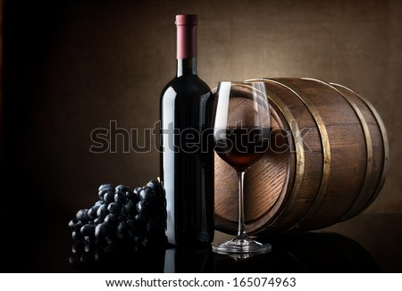 Bottle of red wine, grapes and wooden barrel - stock photo