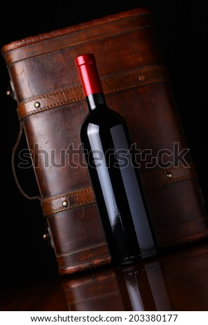 Bottle of red wine with a wooden box in the background - stock photo