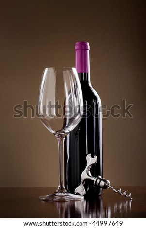 Bottle of red wine with  glass and a corkscrew in a dark wine cellar - stock photo