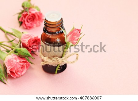 Bottle of rose essence with paper label and rose bud. Pink background.  - stock photo