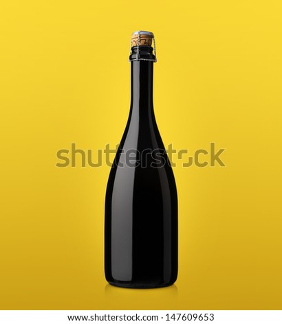 bottle of sparkling wine with cork on a colored background yellow - stock photo