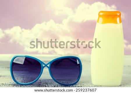Bottle of suntan cream with sunglasses on table Bottle with suntan cream on table isolated on white - stock photo