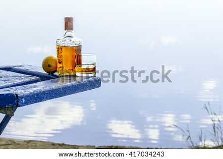 Bottle of tequila and tumbler with lemon on a shore of lake - stock photo