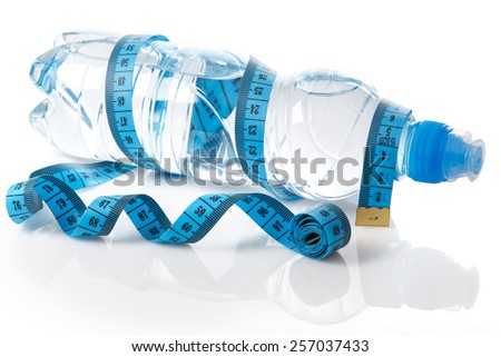 Bottle of water and measure tape on white background - stock photo