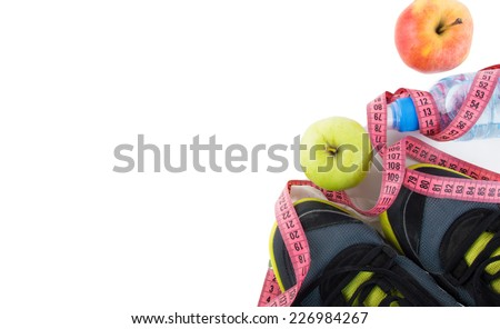bottle of water, measuring tape, apples and sneakers - stock photo