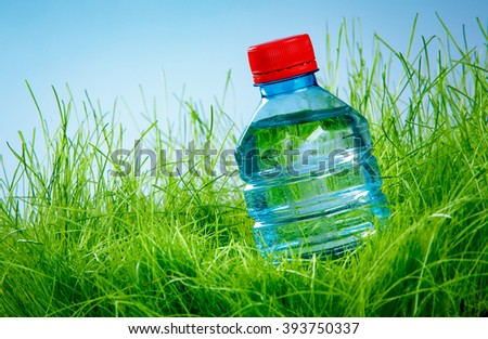 Bottle of water on the green grass - stock photo