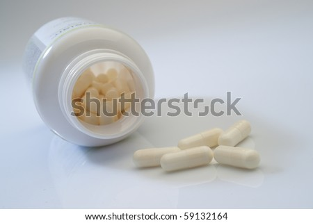 Bottle of white pills and some pills - stock photo