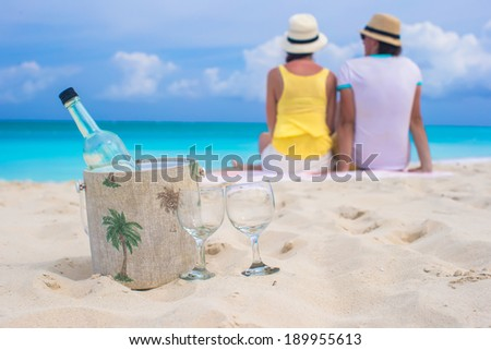 Bottle of white wine and two glasses background happy couple on sandy beach - stock photo