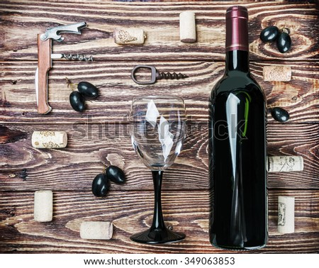 Bottle of wine and accessories on a wooden table - stock photo
