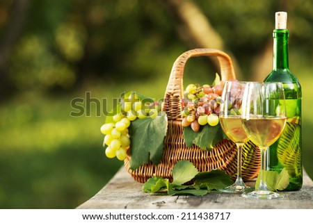 Bottle of wine and grapes on a wooden table. Bottle and full glasses of young white wine are standing on an old wooden table near the basket full of rich organic grapes. New harvest. Space for text - stock photo