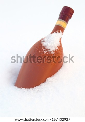 bottle of wine chilling in snow bank - stock photo