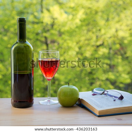 bottle of wine green apple eyeglasses and book on table in the garden - stock photo
