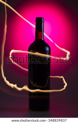 Bottle of wine on the red and pink background with flames - stock photo