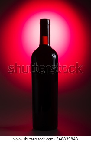 Bottle of wine on the red background  - stock photo