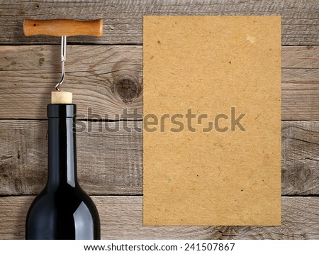 Bottle of wine with corkscrew and blank paper on wooden background - stock photo