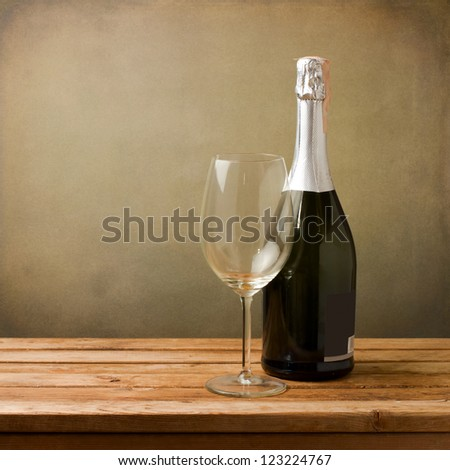 Bottle of wine with empty glass on wooden table - stock photo