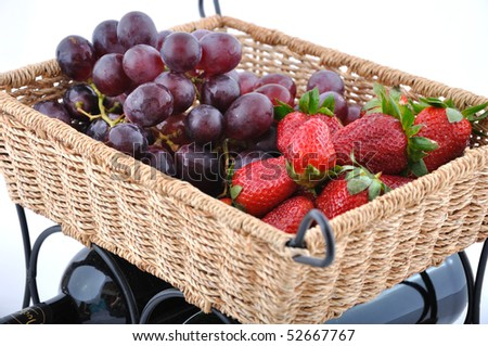Bottle of wine with fruits in straw basket - stock photo