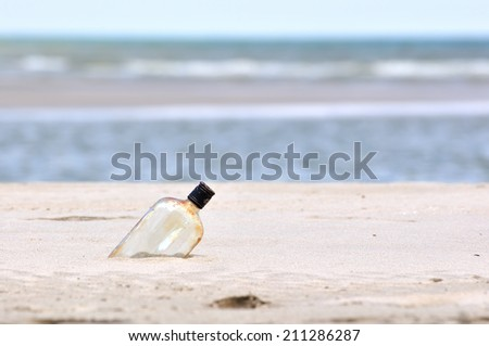 Bottle on a sand beach - stock photo