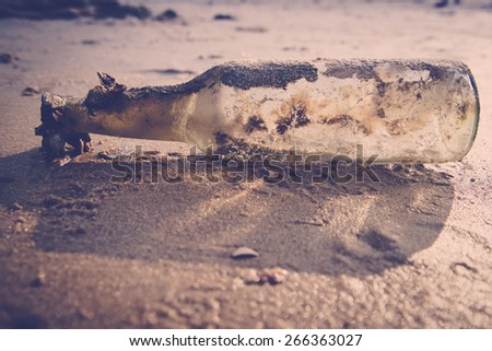 bottle on the sand (bottle on the beach) - stock photo