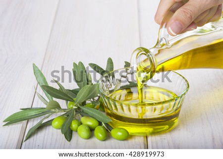 Bottle pouring virgin extra olive oil in a glass bowl - stock photo