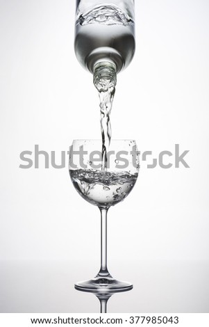 bottle pouring water in glass with bubbles on white background - stock photo
