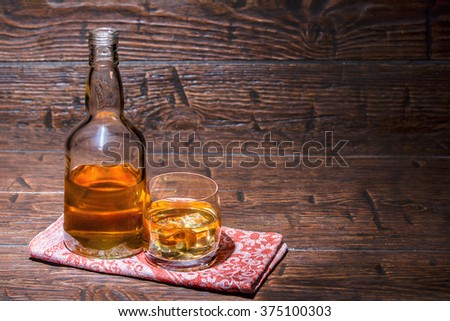 Bottle with a glass with whiskey and ice cubes on the napkin - stock photo
