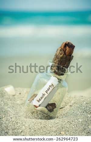 bottle with a message beach party on white sand beach over blue sea and sun light. - stock photo