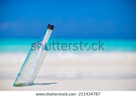 Bottle with a message buried in the white sand - stock photo